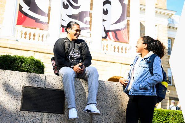 Taking a break before their next class, undergraduate students Andres Ramirez and Isabella Christy talk in front of Bascom Hall